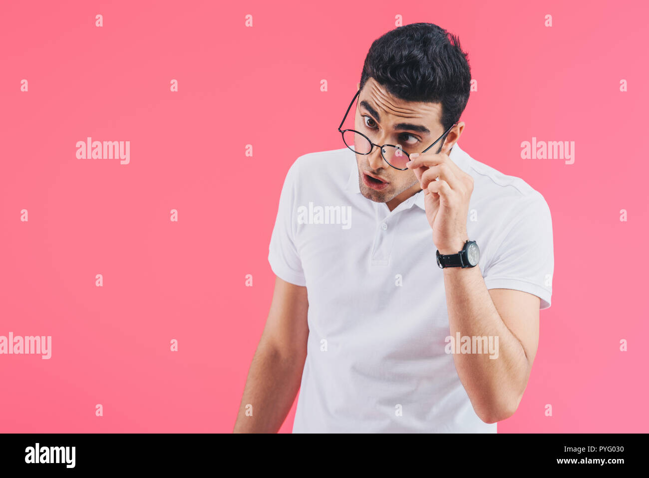 handsome man grimacing and touching glasses isolated on pink - Stock Image