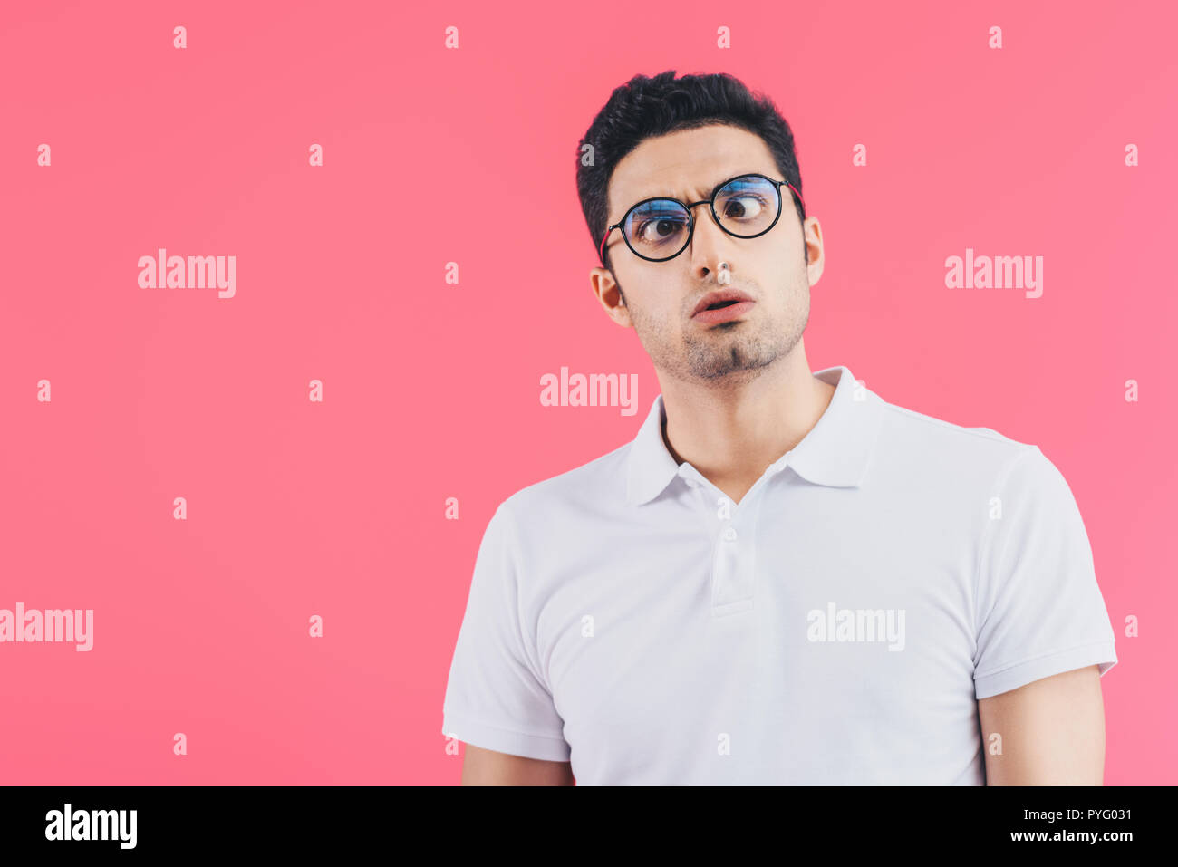 handsome man in glasses grimacing isolated on pink - Stock Image