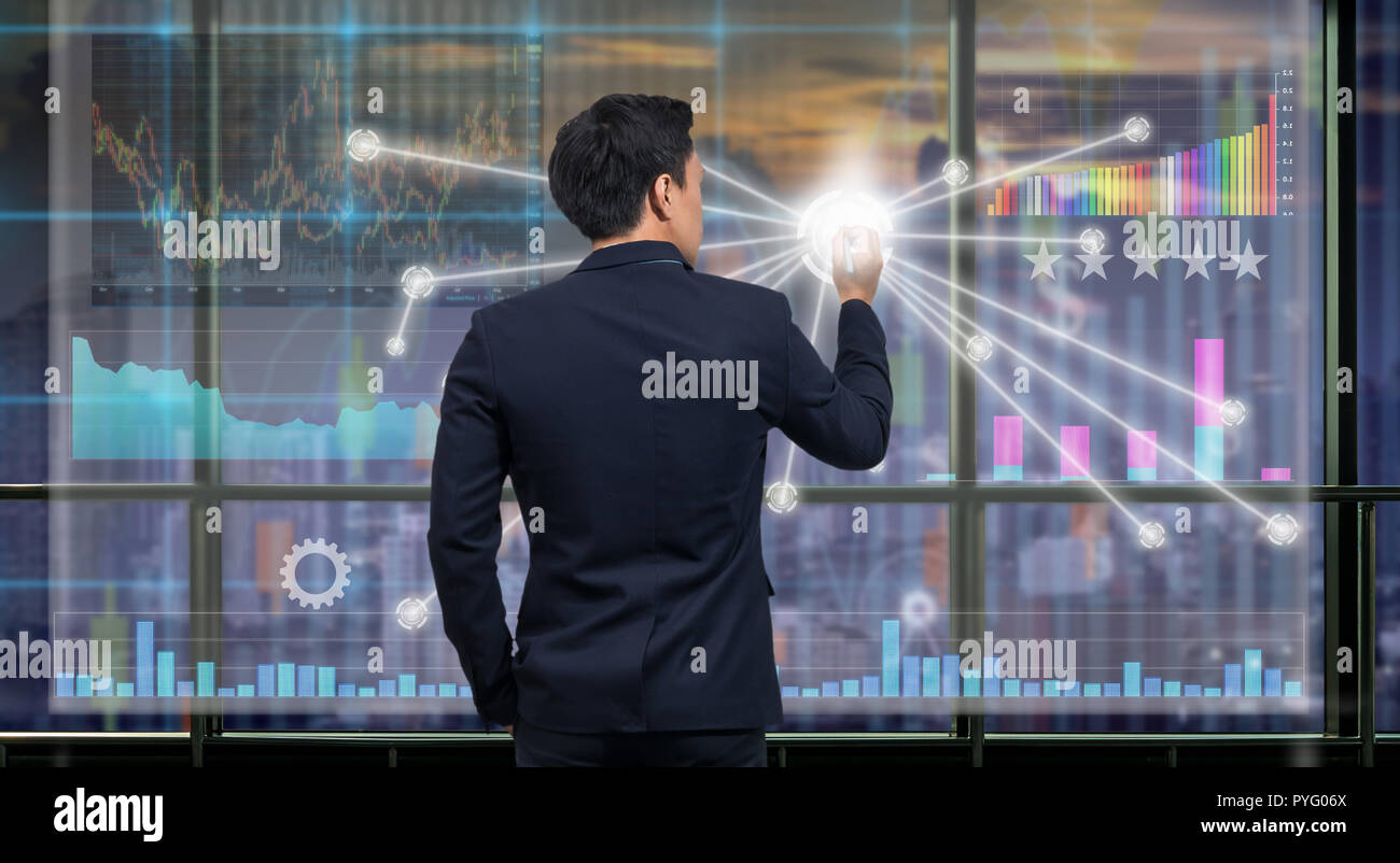 Back side of Businessman drawing the Technical information and trading graph over the virtual screen on the blurred of cityscape background out off wi - Stock Image