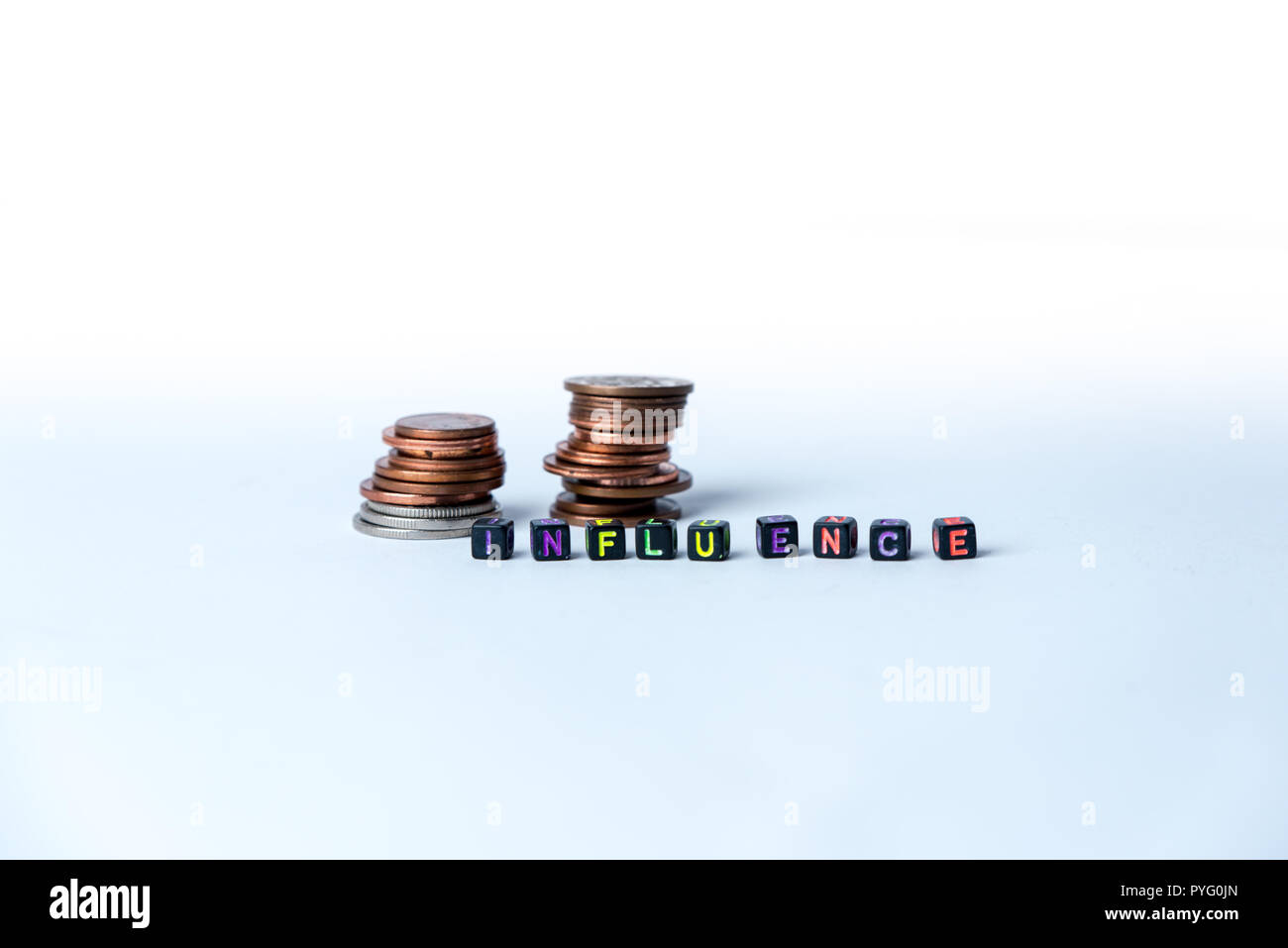 Stack of coins and text influence, made with small blocks on white background - Stock Image
