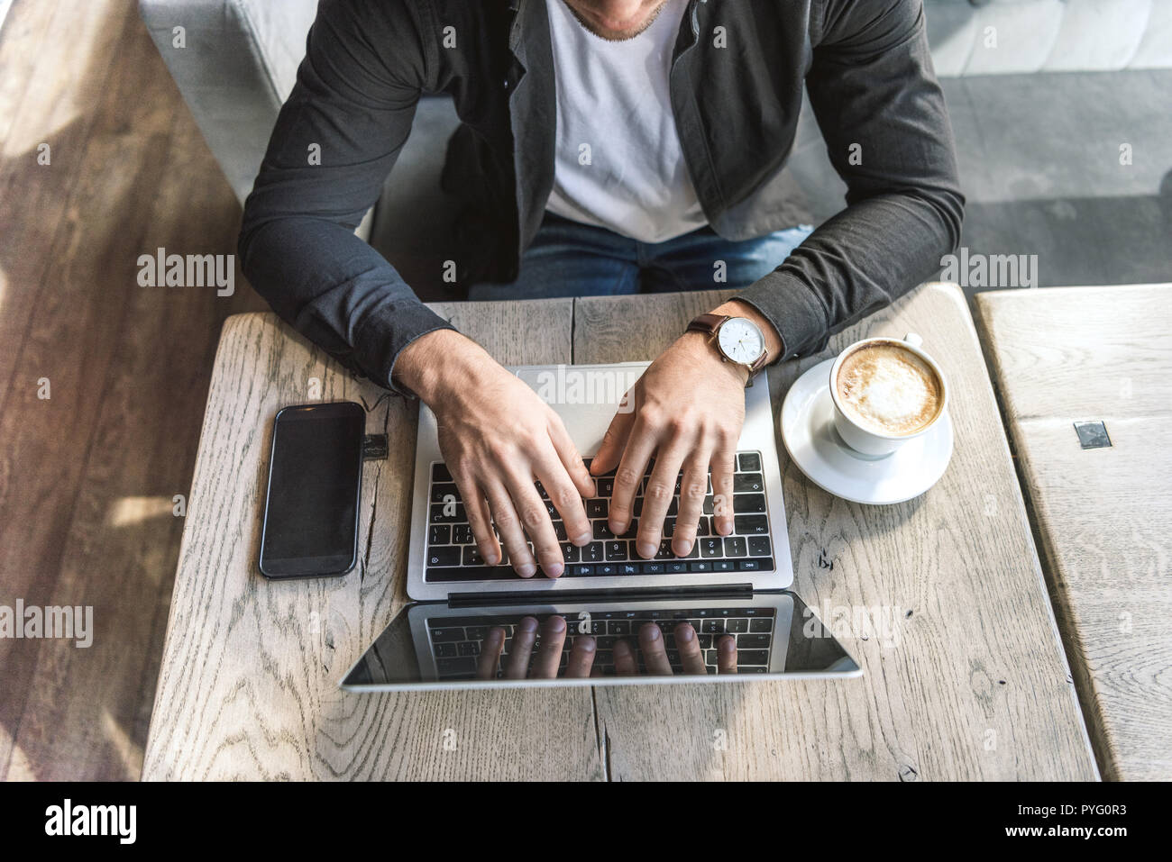 high angle view of young freelancer working with laptop in cafe - Stock Image