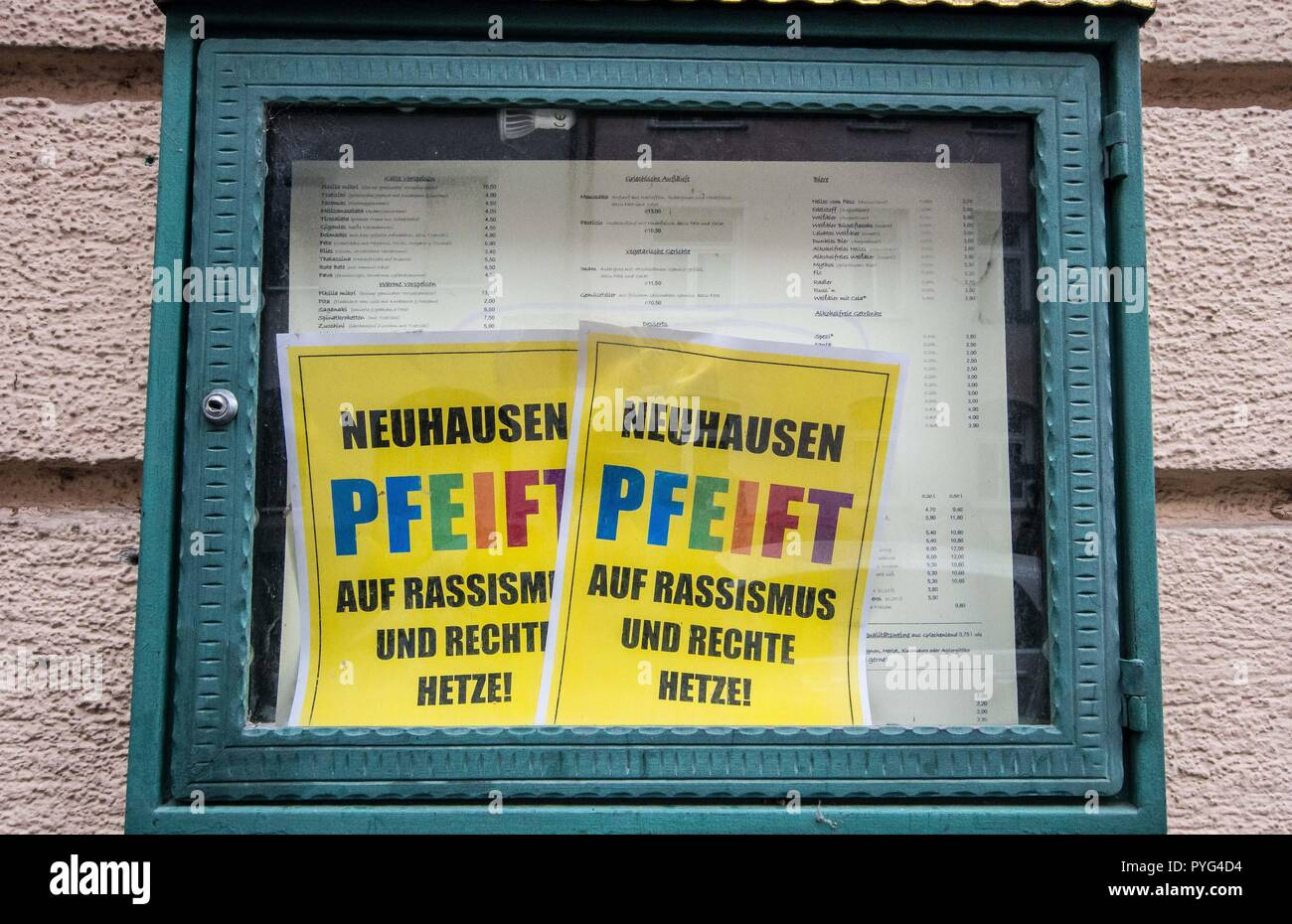 """Munich, Bavaria, Germany. 27th Oct, 2018. A restaurant displays ''Neuhausen Pfeift'' signs in their display case as part of a business action against Pegida. Attempting to draw more followers and expand PEGIDA into Bavaria, """"Pegida Dresden"""""""" announced an appearance by founders LUTZ BACHMANN and SIEGFRIED DAEBRITZ in Munich's Neuhausen district. Ultimately, the two did not arrive, leaving approximately 40 Pegida followers to march against over 450 counter-demonstrators. Pegida Dresden in Munich is actually Pegida Nuremburg who is attempting to expand south to Munich where the rival P Stock Photo"""