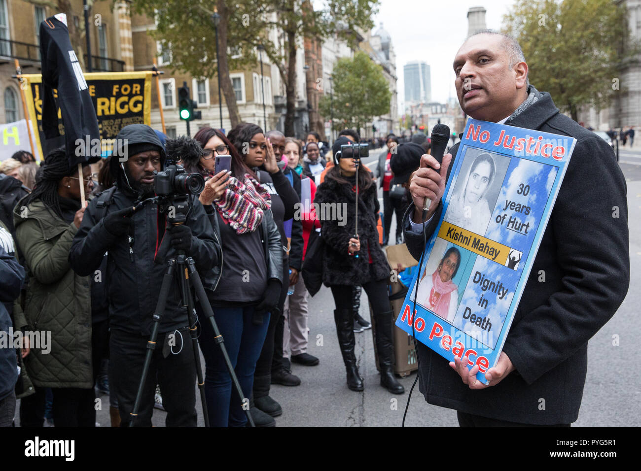 London, UK. 27th October, 2018. Raj Mahay, son of Kishni Mahay, addresses campaigners from the United Families and Friends Campaign (UFFC) taking part in the 20th annual procession to Downing Street in remembrance of family members and friends who died in police custody, prison, immigration detention or secure psychiatric hospitals. Kishni Mahay, 64, was hit by a police car responding to an emergency call in Wolverhampton on 14th March 1989. Credit: Mark Kerrison/Alamy Live News - Stock Image