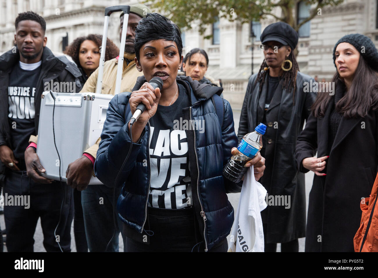 London, UK. 27th October, 2018. Kadisha Brown-Burrell, sister of Kingsley Burrell, addresses campaigners from the United Families and Friends Campaign (UFFC) taking part in the 20th annual procession to Downing Street in remembrance of family members and friends who died in police custody, prison, immigration detention or secure psychiatric hospitals. Kingsley Burrell, 29, died from a cardiac arrest in March 2011 after being restrained whilst detained by West Midlands Police. Credit: Mark Kerrison/Alamy Live News - Stock Image