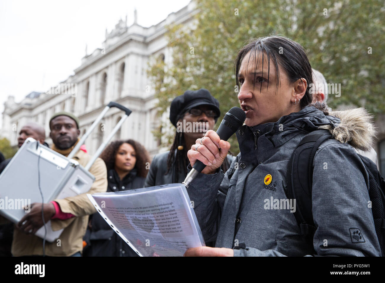 London, UK. 27th October, 2018. Becky Shah of the Hillsborough Justice Campaign, daughter of Inger Shah, addresses campaigners from the United Families and Friends Campaign (UFFC) taking part in the 20th annual procession to Downing Street in remembrance of family members and friends who died in police custody, prison, immigration detention or secure psychiatric hospitals. Inger Shah died in the Hillsborough disaster on 15th April 1989. Credit: Mark Kerrison/Alamy Live News - Stock Image