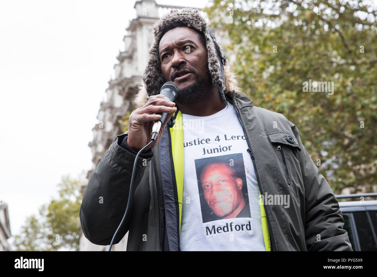London, UK. 27th October, 2018. Dennis Medford, brother of Leroy 'Junior' Medford, addresses campaigners from the United Families and Friends Campaign (UFFC) taking part in the 20th annual procession to Downing Street in remembrance of family members and friends who died in police custody, prison, immigration detention or secure psychiatric hospitals. Junior Medford, 43, died from a heroin overdose at Loddon Valley police station on 2nd April 2017. Credit: Mark Kerrison/Alamy Live News - Stock Image