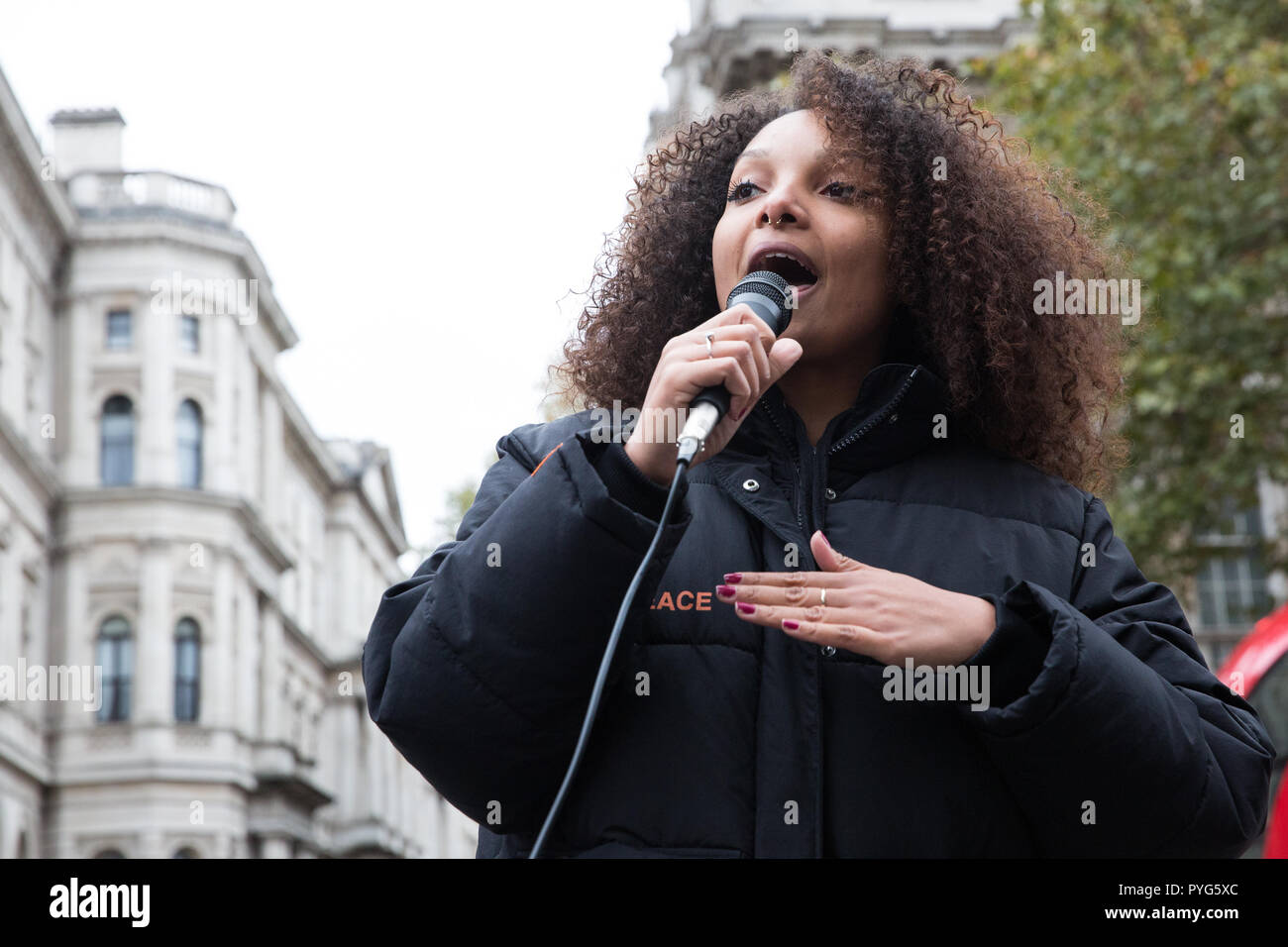 London, UK. 27th October, 2018. A friend of the family of Mark Duggan addresses campaigners from the United Families and Friends Campaign (UFFC) taking part in the 20th annual procession to Downing Street in remembrance of family members and friends who died in police custody, prison, immigration detention or secure psychiatric hospitals. Mark Duggan, 29, was shot by a Metropolitan Police firearms officer in Tottenham, north London, on 4th August 2011. Credit: Mark Kerrison/Alamy Live News - Stock Image