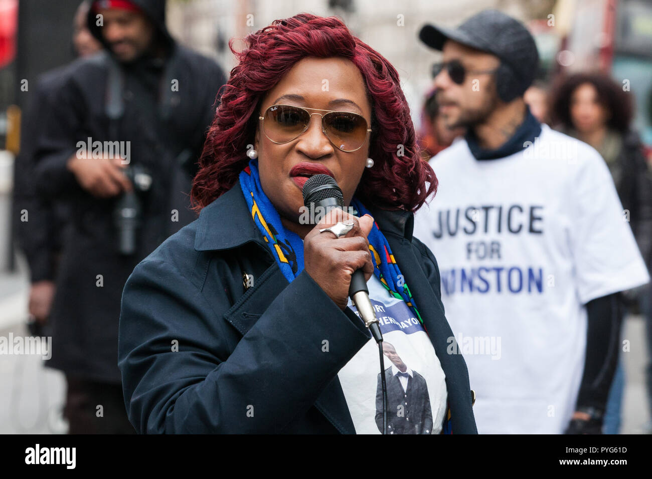 London, UK. 27th October, 2018. A relative of Sheku Bayoh addresses campaigners from the United Families and Friends Campaign (UFFC) taking part in the 20th annual procession to Downing Street in remembrance of family members and friends who died in police custody, prison, immigration detention or secure psychiatric hospitals. Sheku Bayoh died after being detained at a police station in 2015. Credit: Mark Kerrison/Alamy Live News - Stock Image