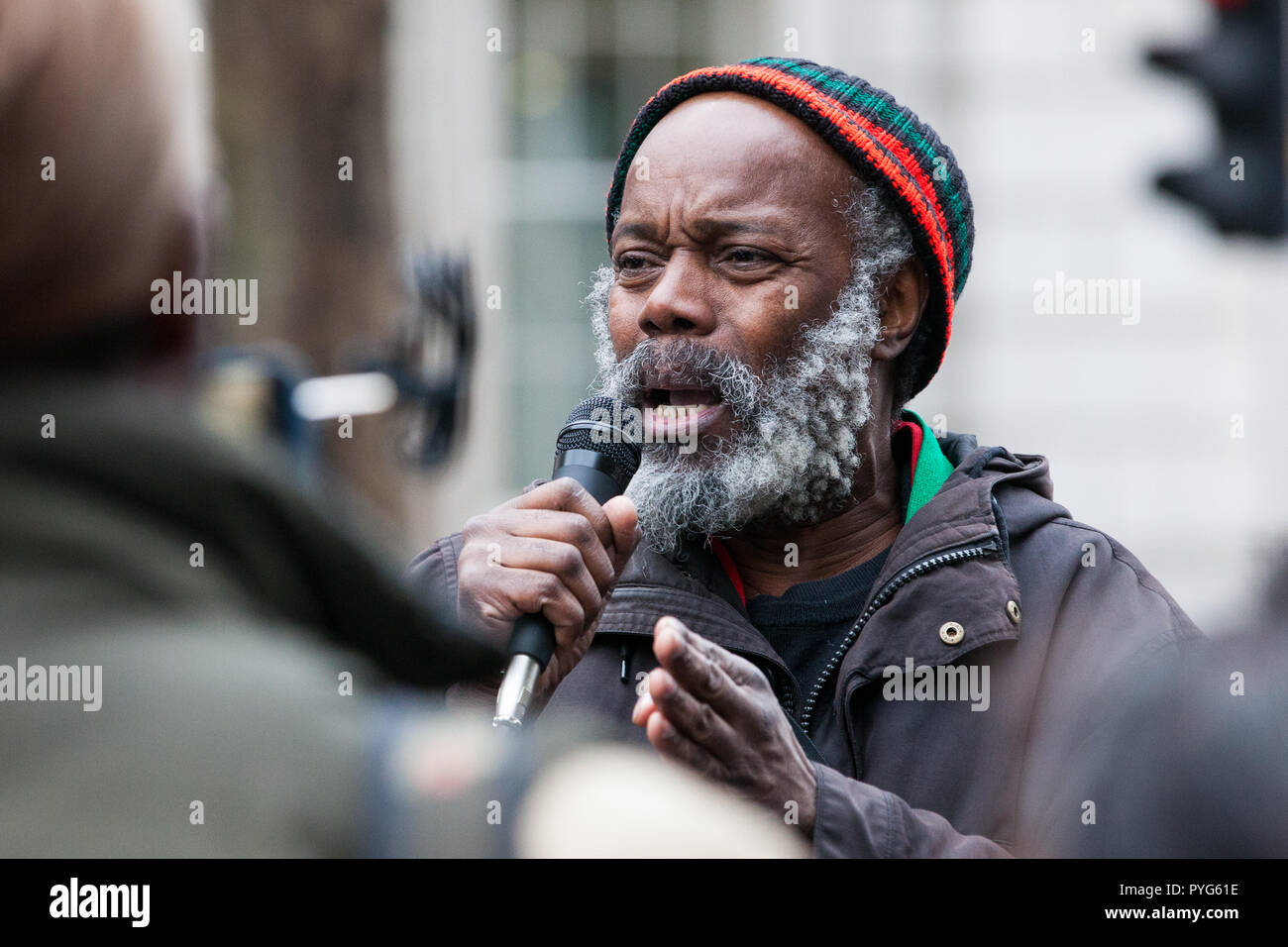 London, UK. 27th October, 2018. Brother Minka of the Pan African Community Forum addresses campaigners from the United Families and Friends Campaign (UFFC) taking part in the 20th annual procession to Downing Street in remembrance of family members and friends who died in police custody, prison, immigration detention or secure psychiatric hospitals. UFFC was set up in 1997 by families who had lost loved ones at the hands of the state with the intention of challenging systemic injustice. Credit: Mark Kerrison/Alamy Live News - Stock Image
