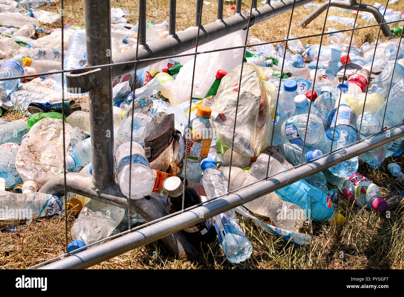 Belgrade, Serbia - June 25, 2017: Plastic bottles tossed by the metal fence. Used empty pet bottles thrown away and left on grass after an open air. Stock Photo