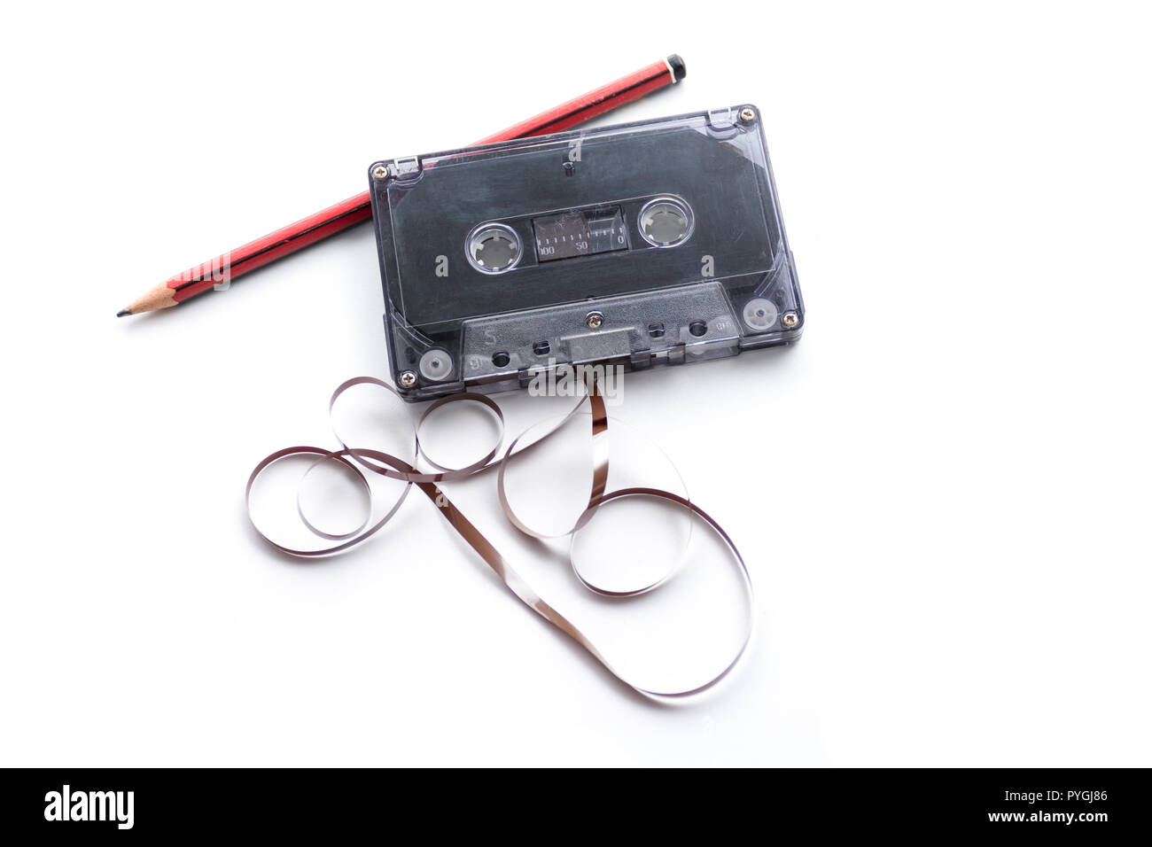 Red pencil and compact cassette with tape coming out - Stock Image