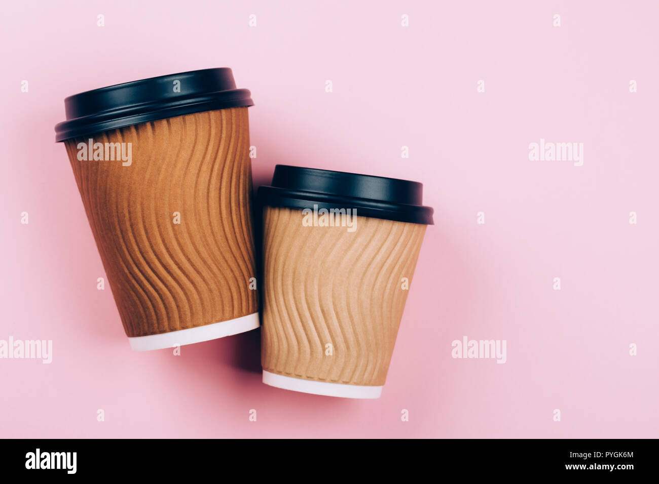 6867b32d68b Two brown craft cups of coffee to go on pastel pink background. Flat lay  style. Place for text.