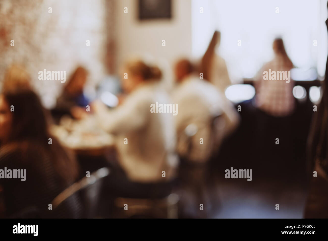 Blurred background of people sitting in modern cafe. - Stock Image