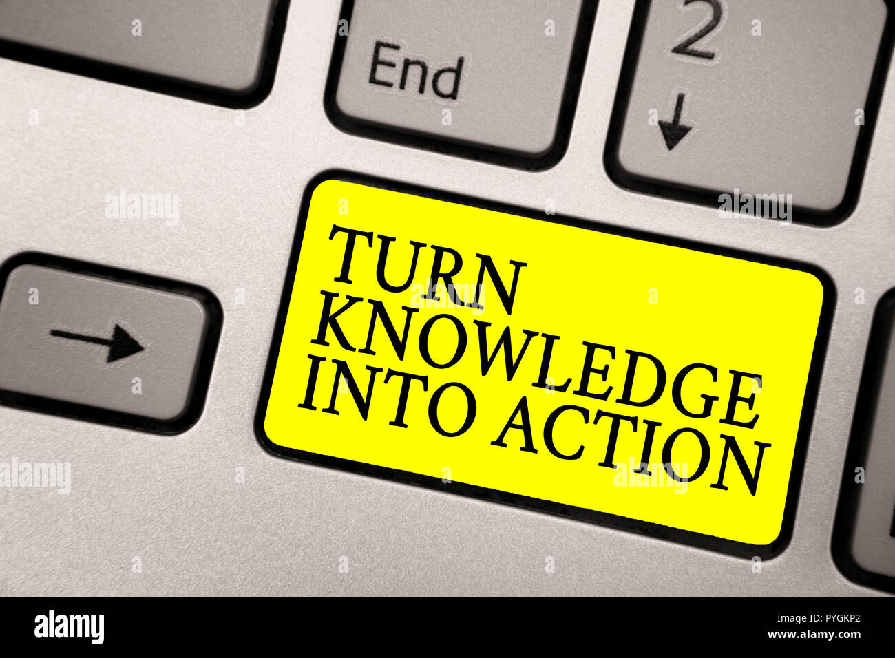 Word writing text Turn Knowledge Into Action. Business concept for Apply what you have learned Leadership strategies Grey silvery keyboard with bright - Stock Image