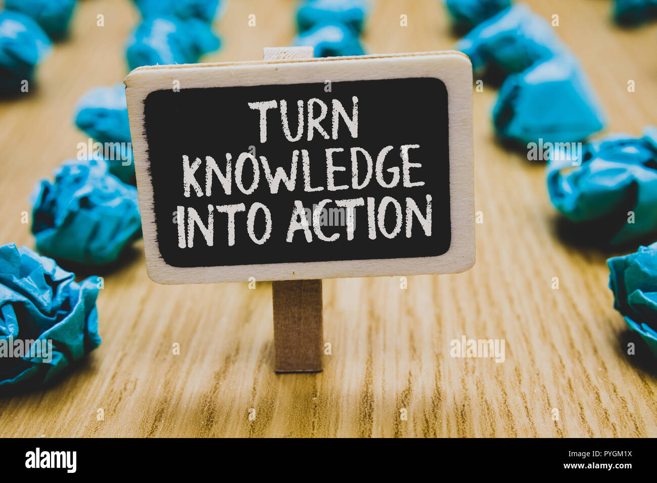 Handwriting text writing Turn Knowledge Into Action. Concept meaning Apply what you have learned Leadership strategies Stand blackboard with white wor - Stock Image