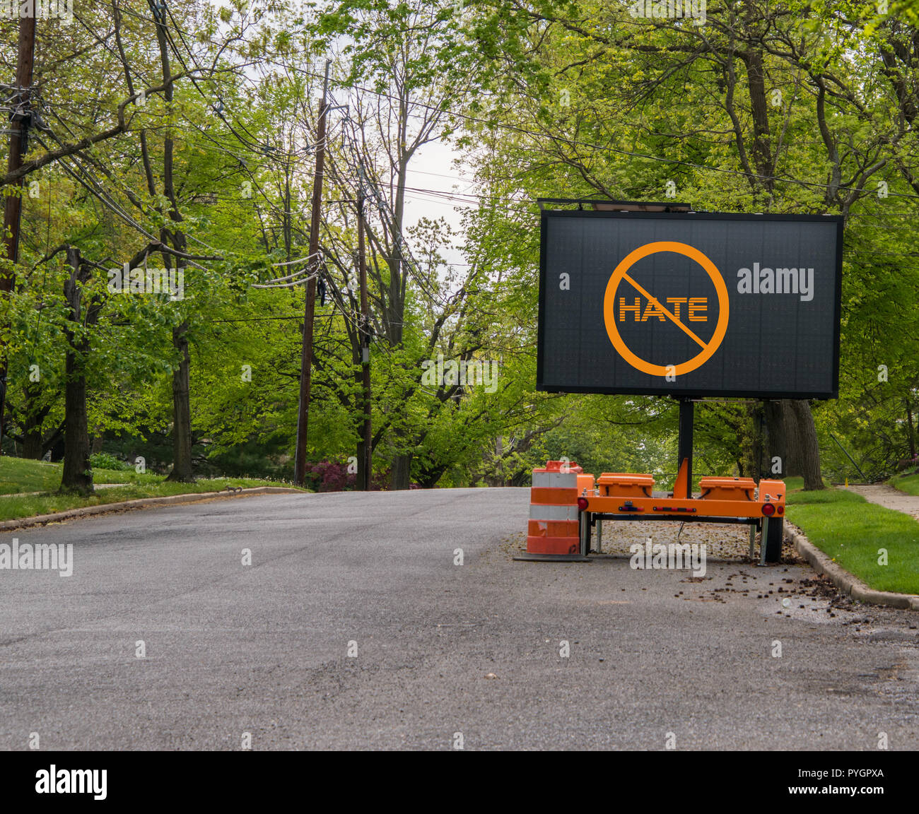 Electric traffic street sign on quiet neighborhood street that has a no hate symbol - Stock Image
