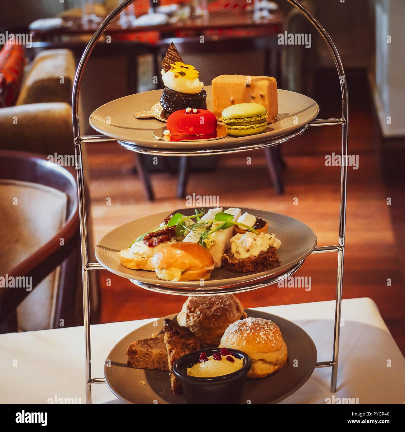 a tiered rack with a complete English afternoon tea  with sweets, savory sandwiches, scones, clotted cream, served - Stock Image