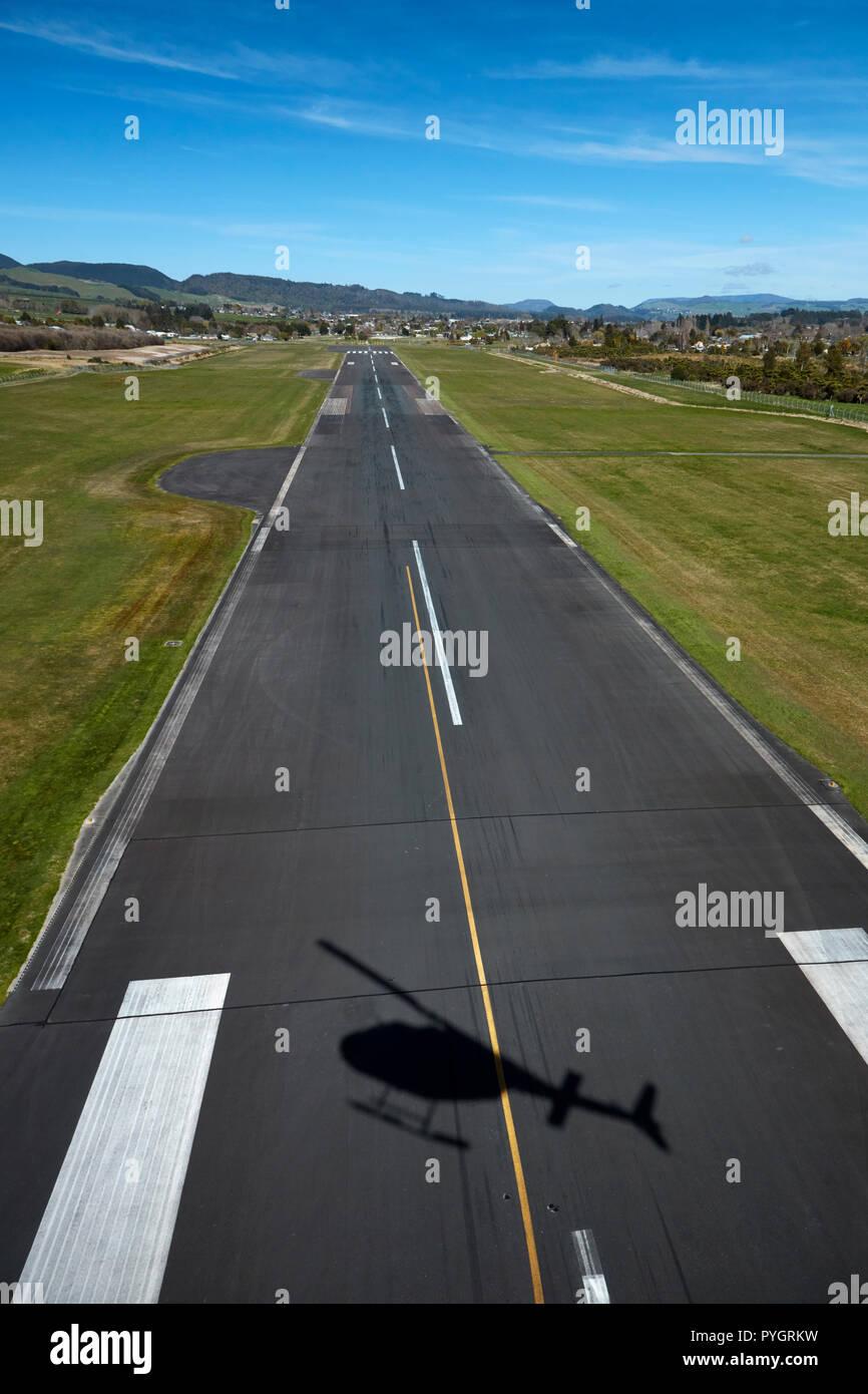 Helicopter shadow on runway, Rotorua Airport, and Lake Rotorua, Rotorua, North Island, New Zealand - aerial - Stock Image