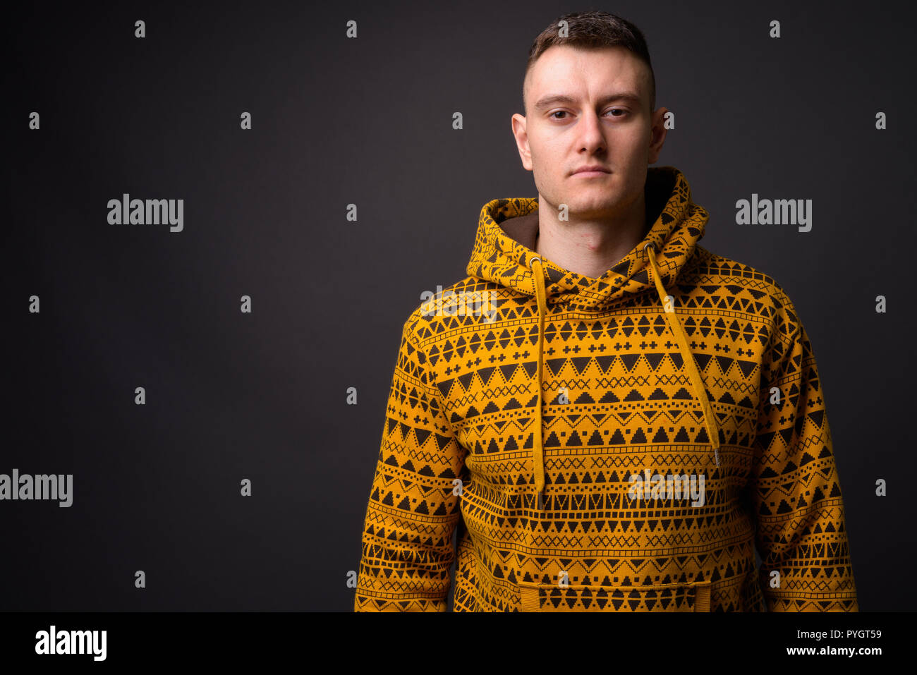 680f1892 Portrait of young handsome man wearing yellow hoodie Stock Photo ...