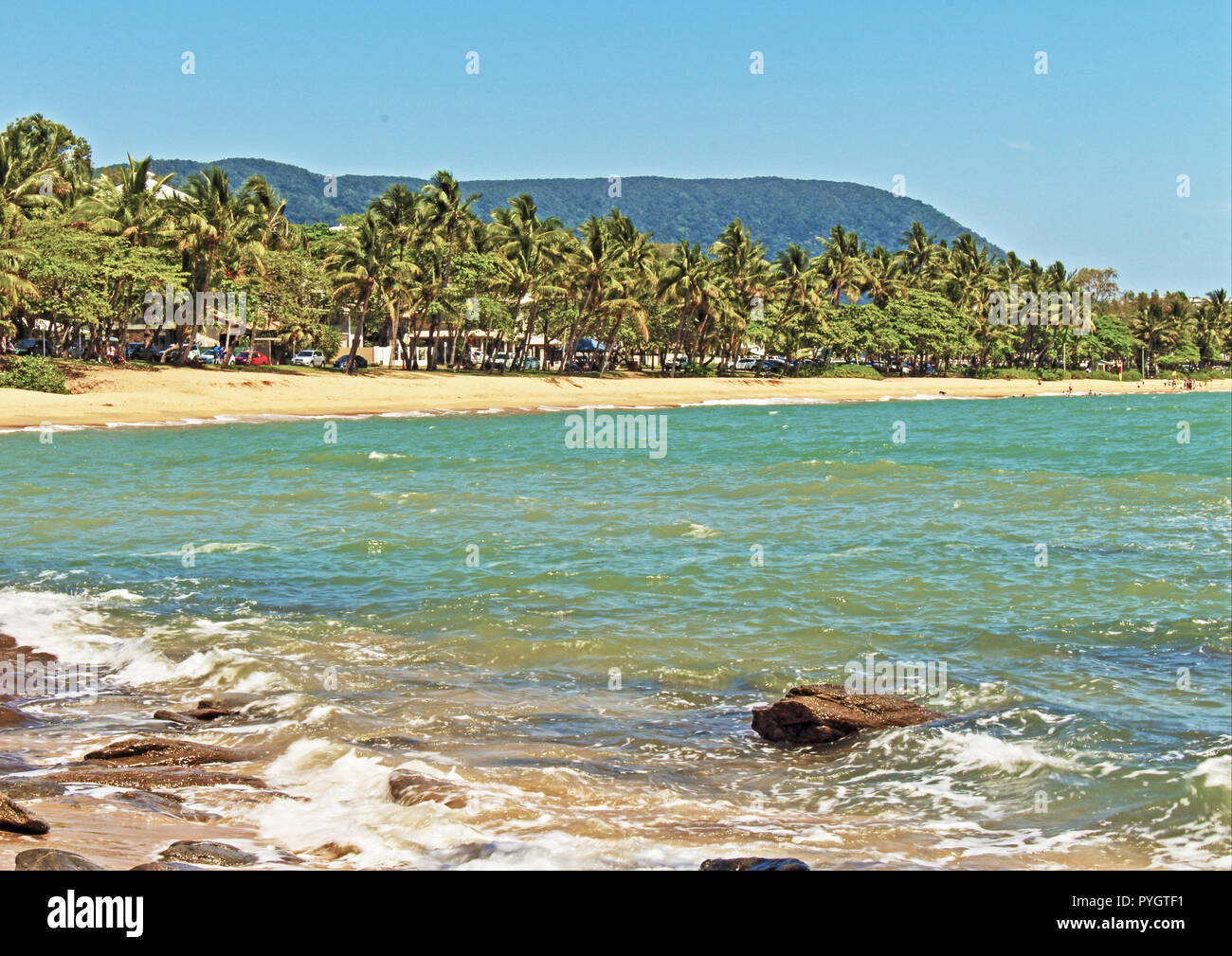 The beautiful palm tree lined beach and esplanade as seen from across the cove at Trinity Beach, Cairns QLD Australia - Stock Image