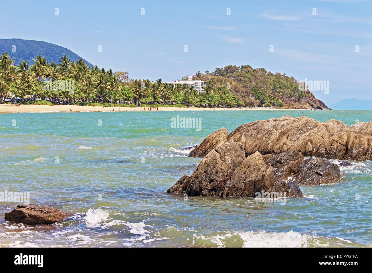 The view across the cove to the beach and headland in Trinity Beach, one of the northern beaches in Cairns QLD Australia - Stock Image