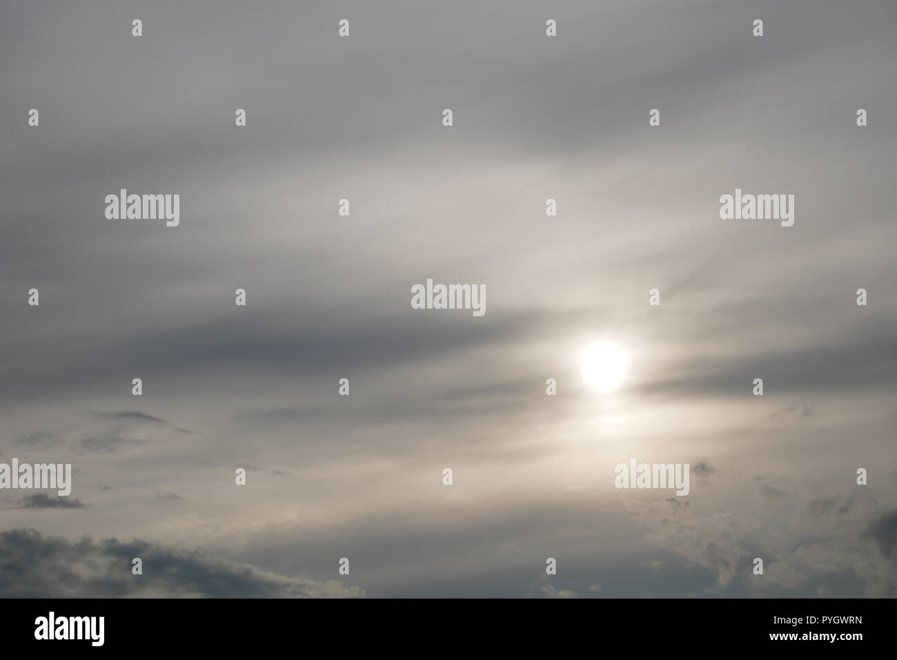 Gray moody clouds and the sun shines through the overcast - Stock Image