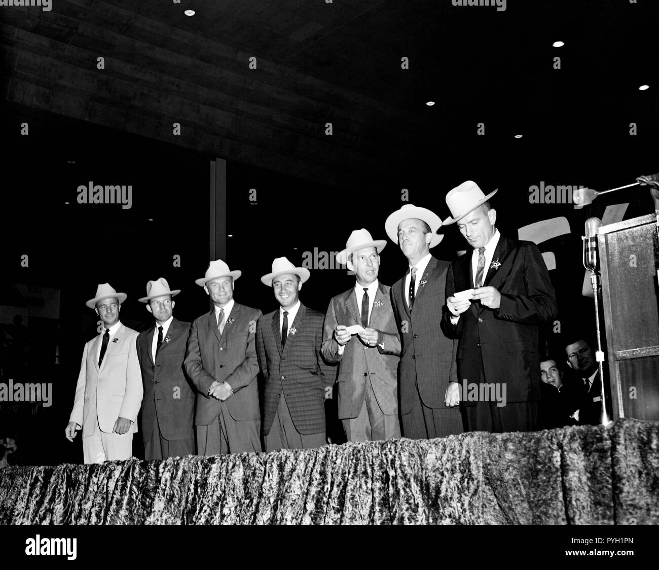 (4 July 1962) --- The original seven Mercury astronauts, each wearing new cowboy hats and a badge in the shape of a star, are pictured on stage at the Sam Houston Coliseum. A large crowd was on hand to welcome them to Houston, Texas. Left to right are astronauts M. Scott Carpenter, L. Gordon Cooper Jr., John H. Glenn Jr., Virgil I. Grissom, Walter M. Schirra Jr., Alan B. Shepard Jr., and Donald K. Slayton. Sen. John Tower (R.-Texas) is seen in far right background. - Stock Image