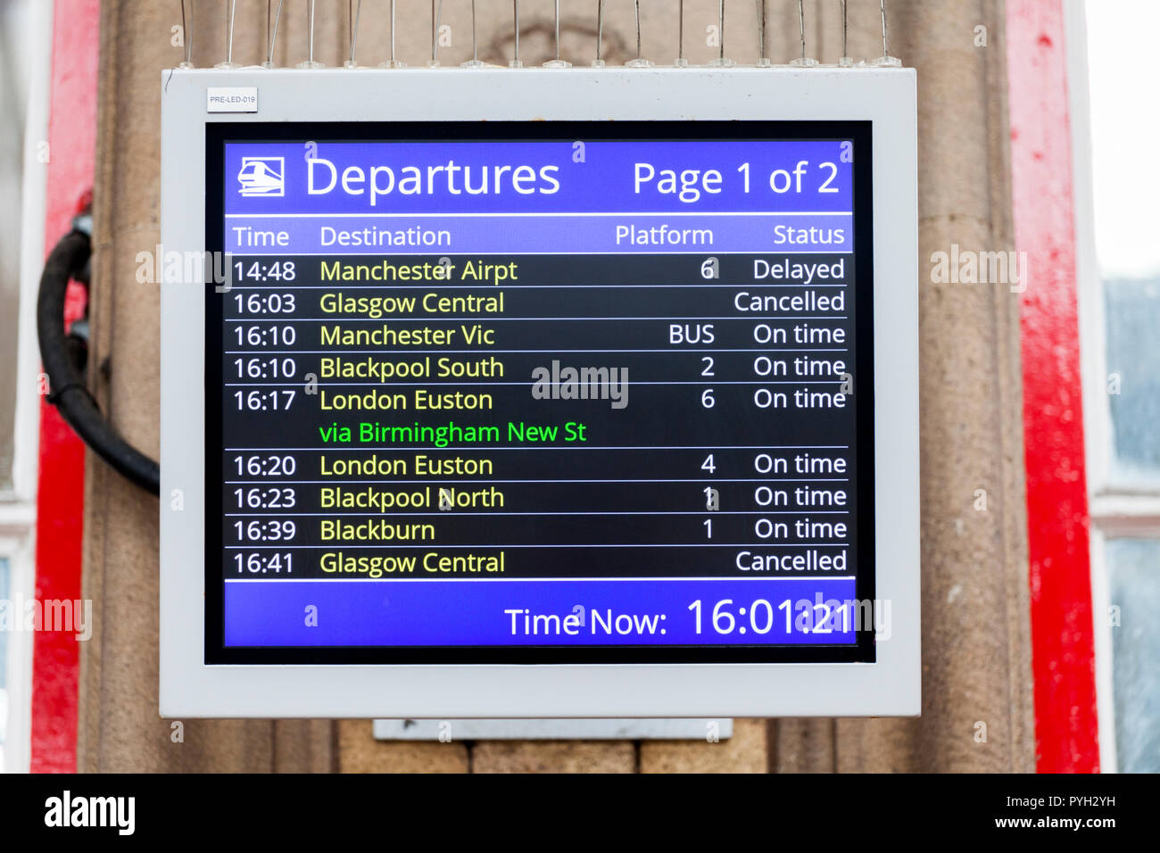 Departure screen at Preston railway station showing cancelled, delayed trains and rail replacement bus services - Stock Image