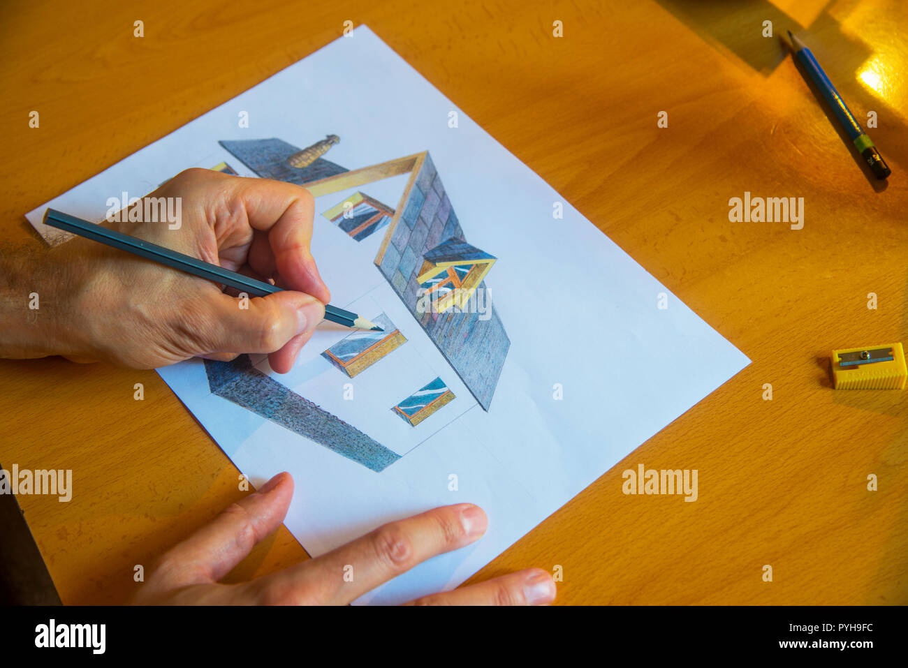 Man drawing a house with color pencils. - Stock Image