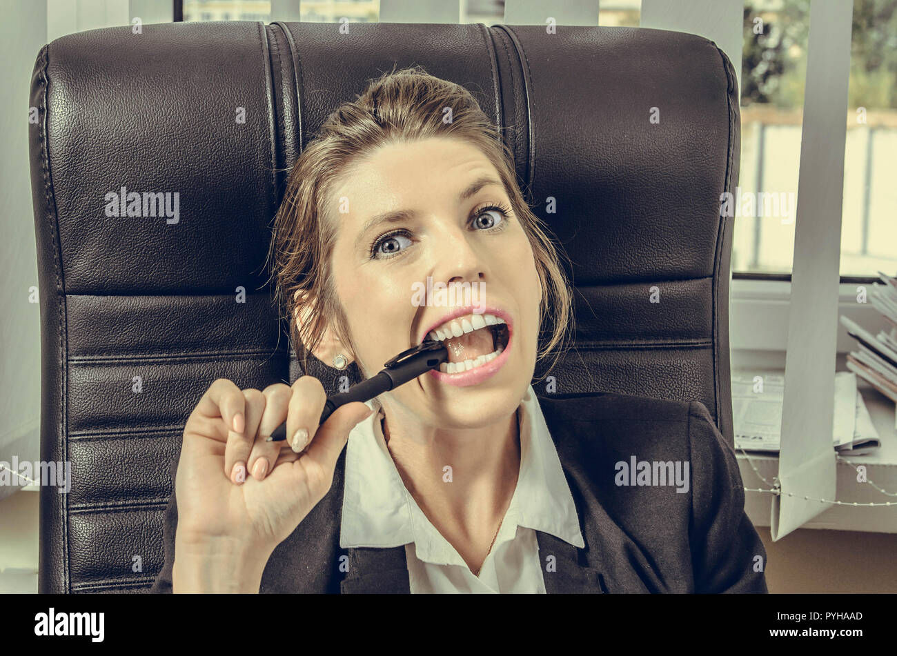 girl in a business suit grimacing and biting a pen. Office life - Stock Image