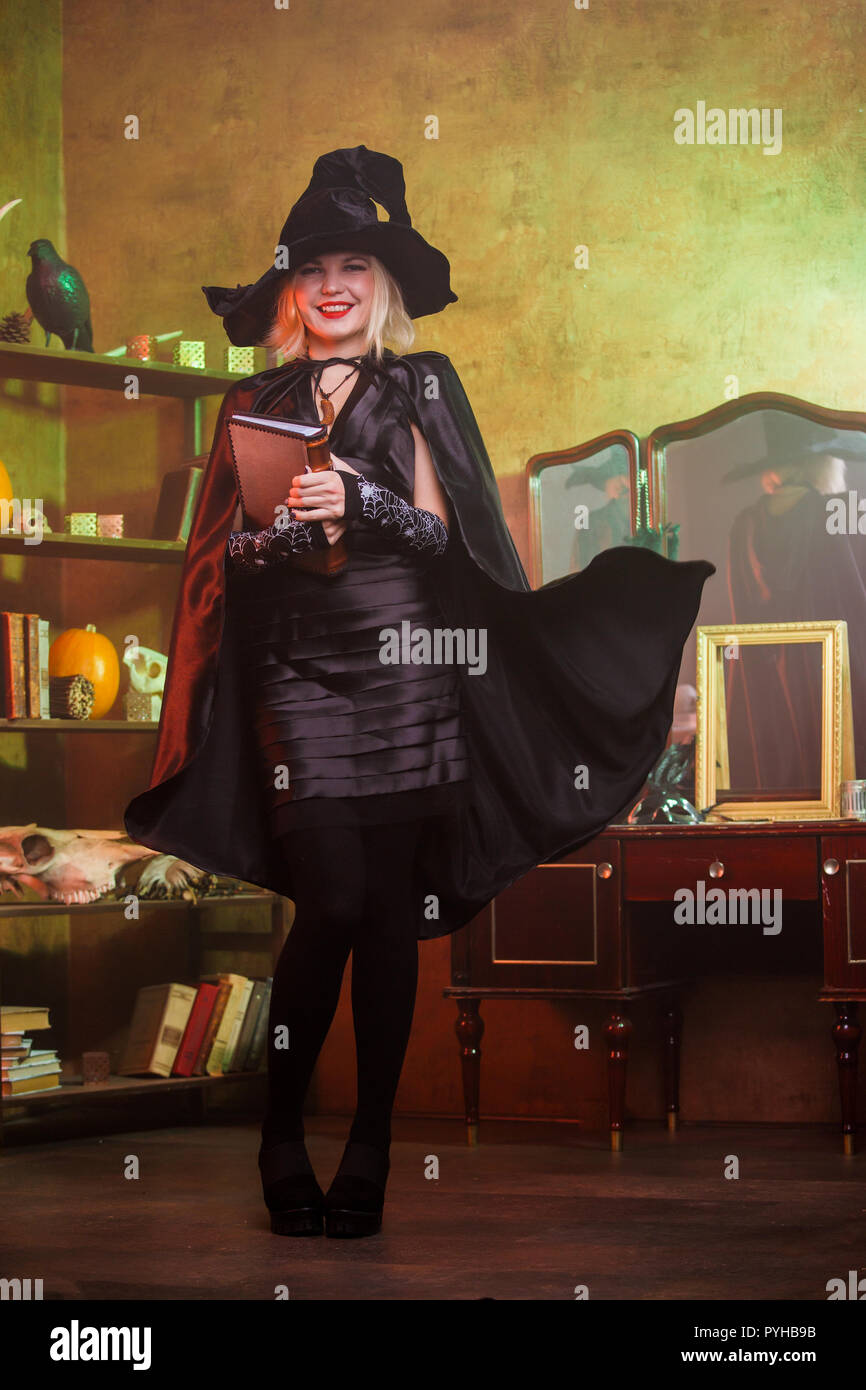 Picture of witch in black hat, dress, developing cloak - Stock Image