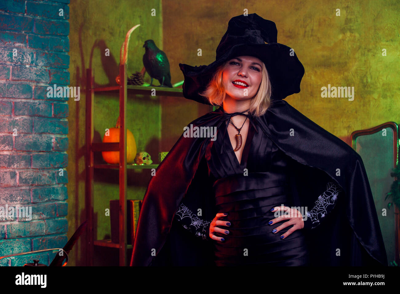 Photo of smiling witch in black hat, dress on background of rack with pumpkin and crow - Stock Image