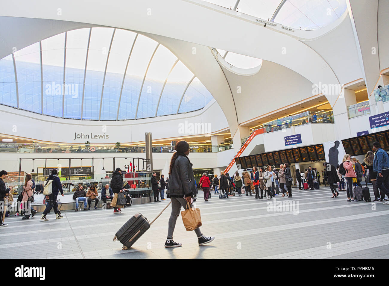 Birmingham New Street Station. Woman with travel suitcase. People waiting for trains. Shop John Lewis. - Stock Image