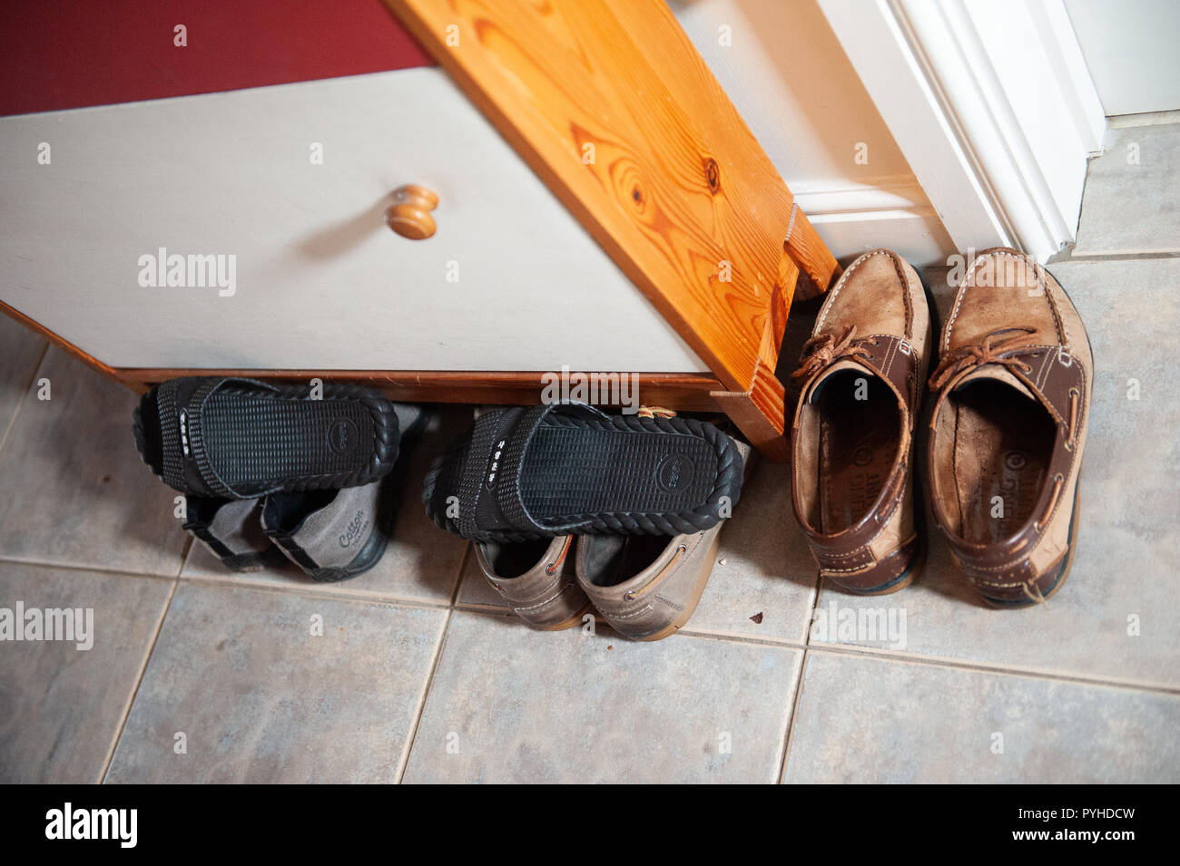 Collection of footwear around and under a shoe cupboard. - Stock Image