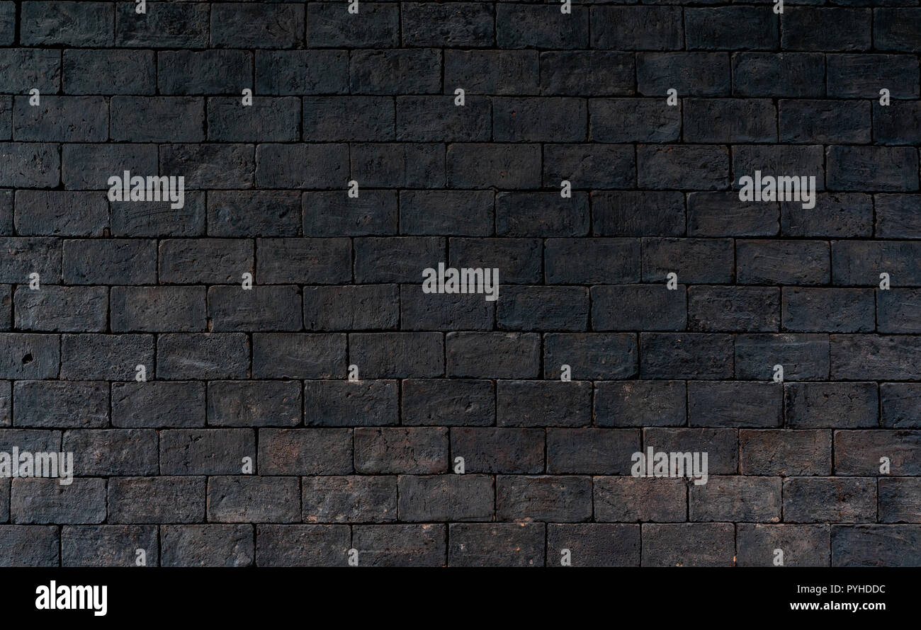 Black and brown brick wall rough texture background with space for text. Background for death, sad, hopeless and despair concept. Dark brick wall for  - Stock Image
