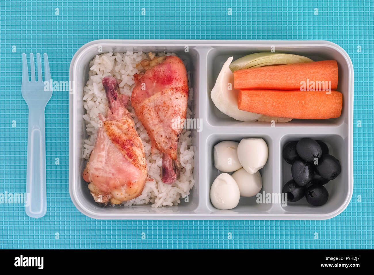 Lunch box with rice and chicken, quail eggs, black olives and vegetables. Top view. Natural lighting. Close up. - Stock Image