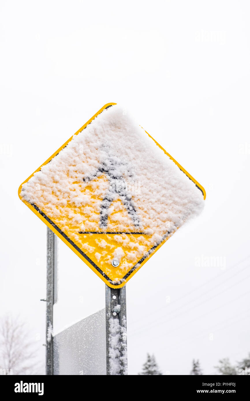 Pedestrial crossing sign covered with wet new snow.  Concept for first snow or slippery conditions. - Stock Image