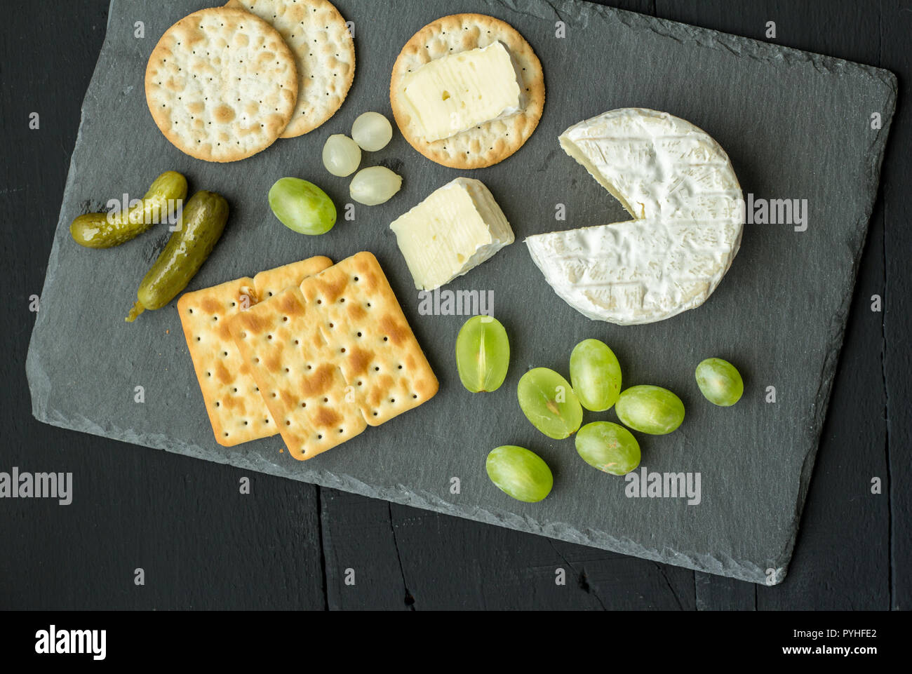 Camembert cheese and slices on water crackers with dill pickles and green grapes on black slate cheese board - Top view studio photograph - Stock Image