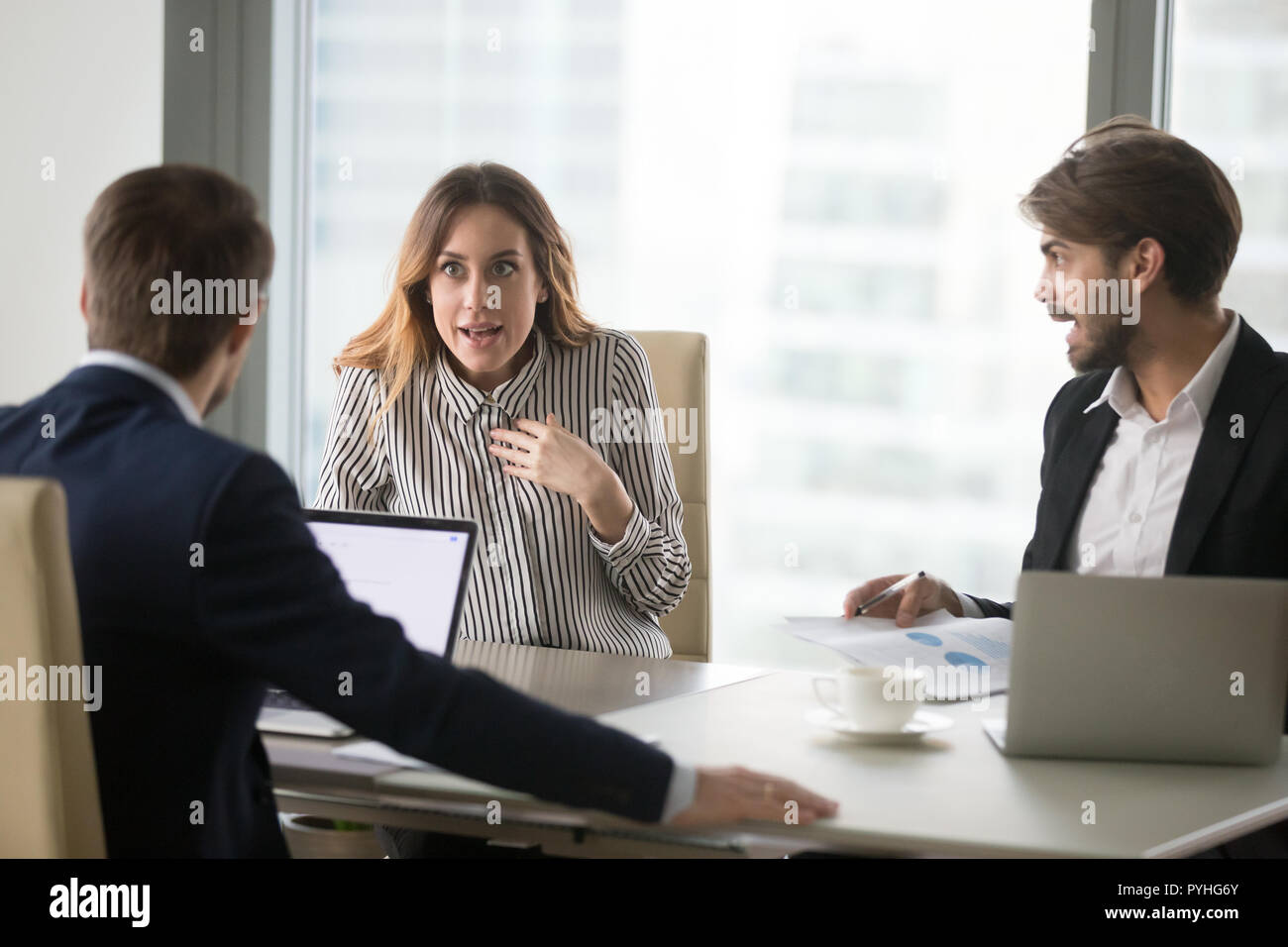 Angry man shouting at indignant female colleague. - Stock Image