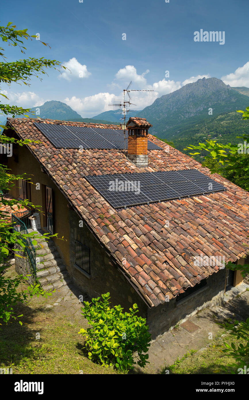 Solar panels and chimney pot on the roof of an old Italian cottage (portrait). - Stock Image
