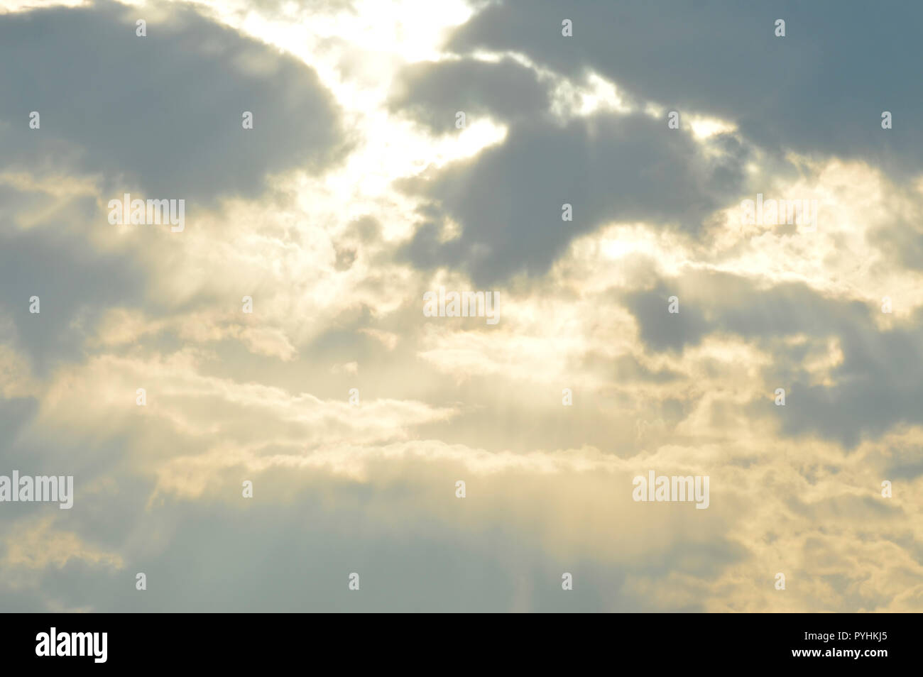 Yellow sunlight streaming through a light cloud cover. - Stock Image