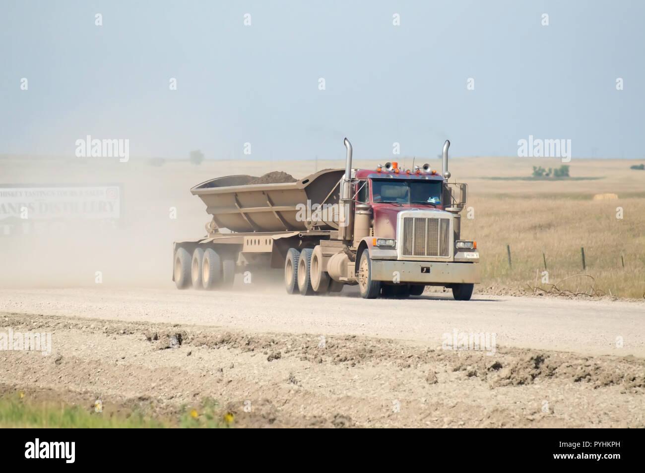A side dumping semi truck hauling dirt down a dusty desert road. - Stock Image