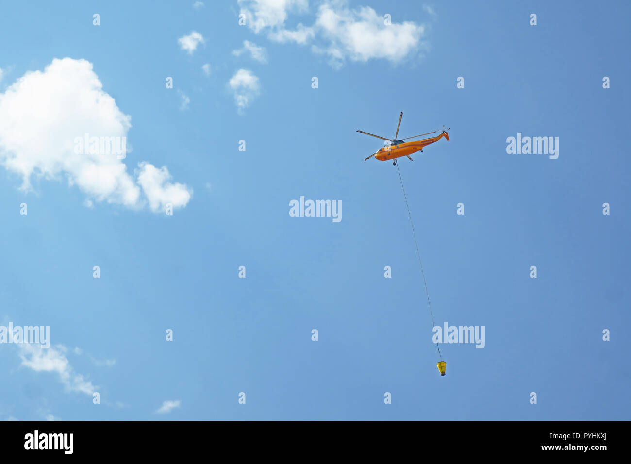 A yellow fire fighting helicopter flying to deliver water in Utah. - Stock Image