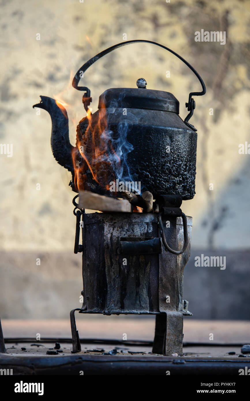 Old metal tea pot in flames a fire stove - Stock Image
