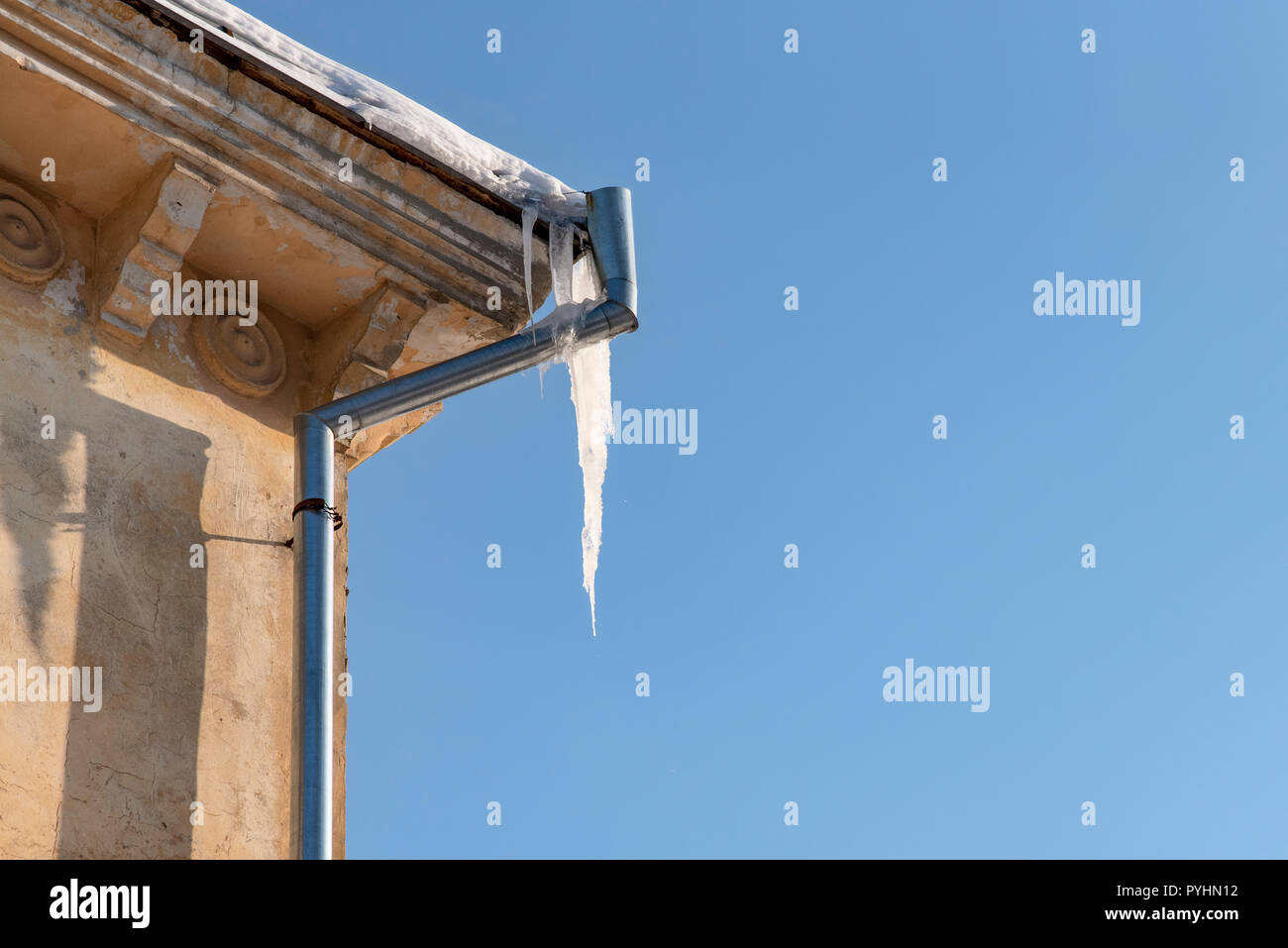Winter threats: icicles hang from roof of building. Danger for passers, threat of death and injury from icicles - Stock Image