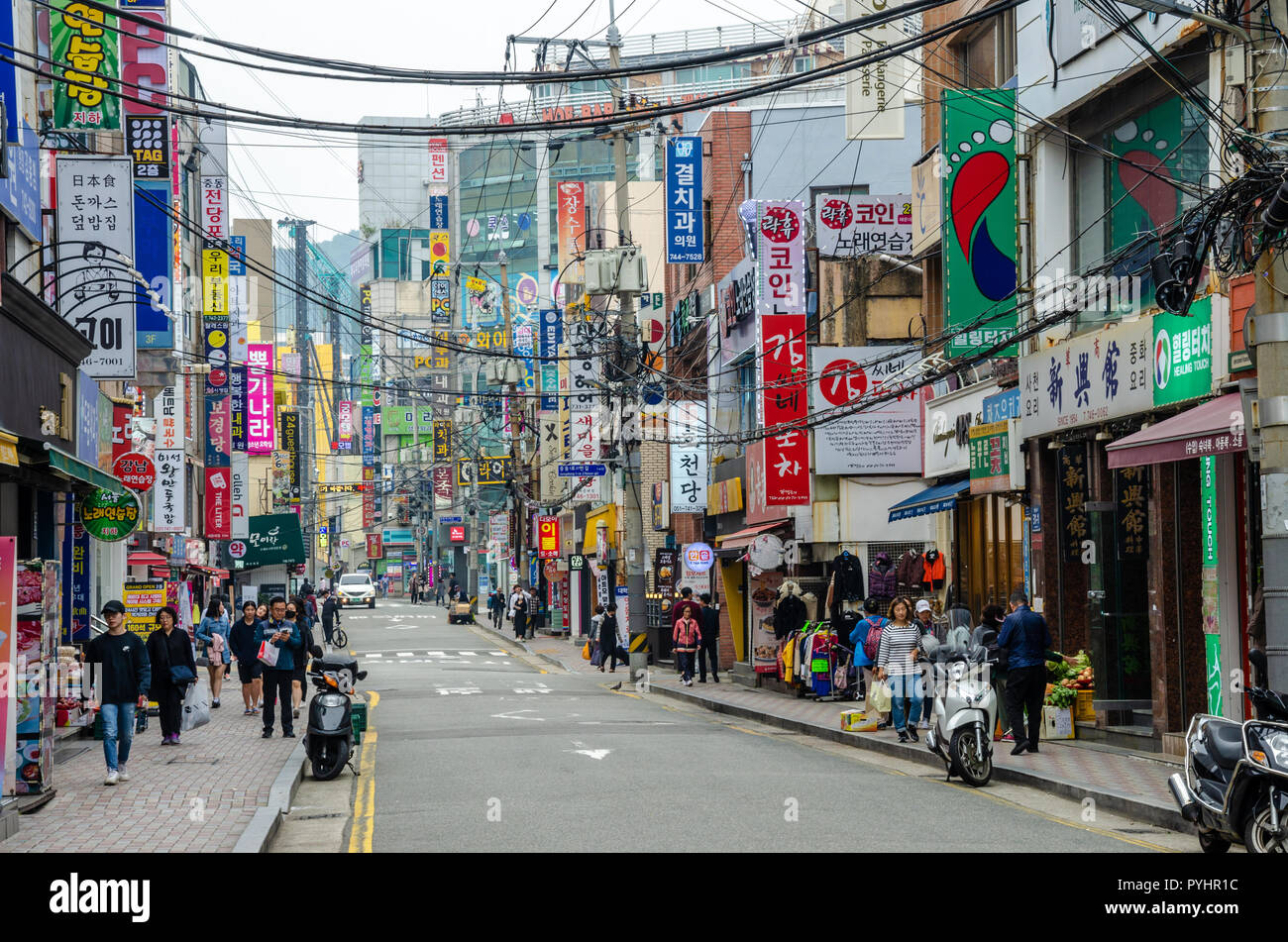 A street with many shops in Haeundae, Busan, South Korea. Overhead power cables criss-cross the street. - Stock Image