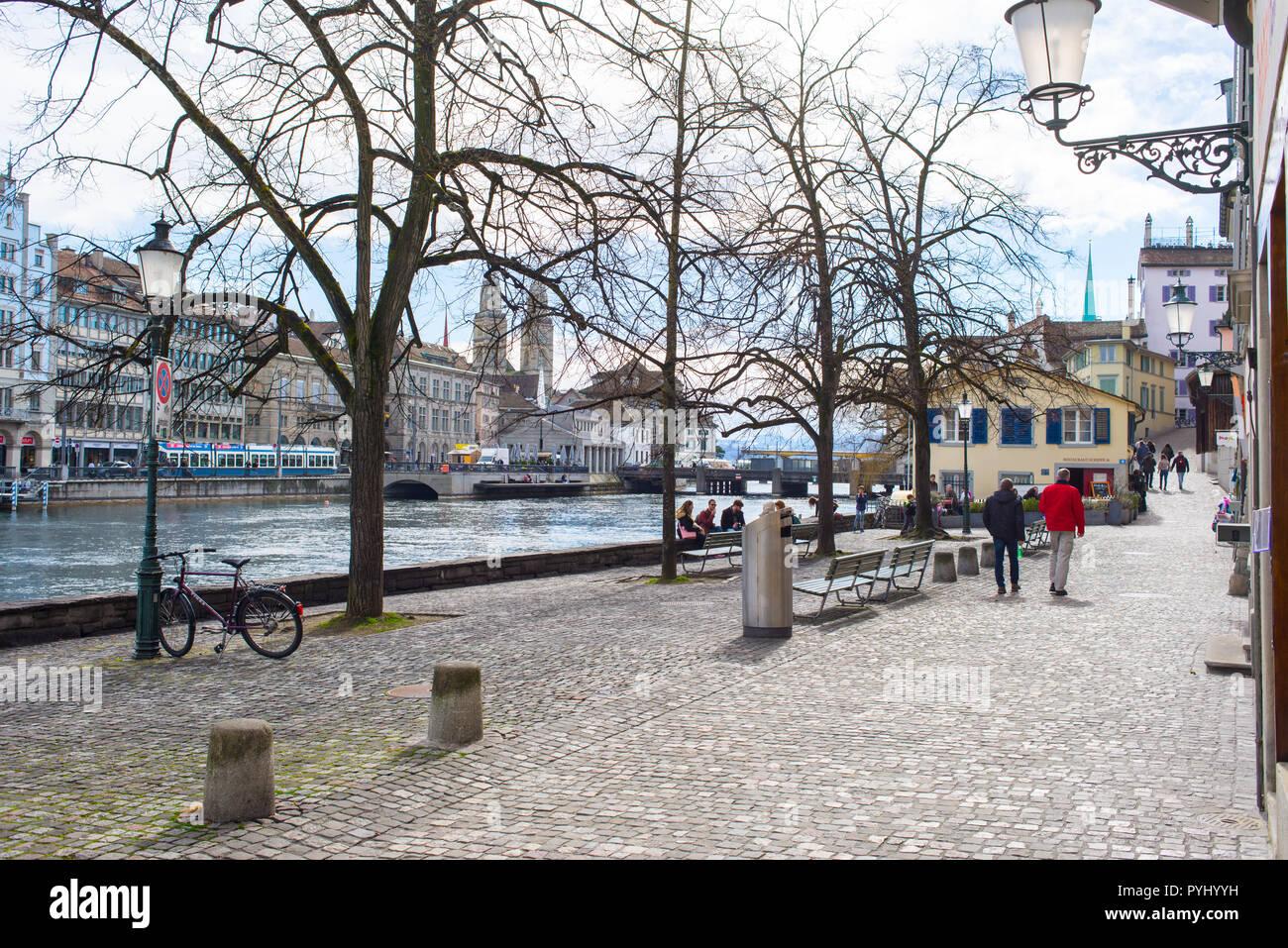 Zurich, Switzerland - March 2017: People walking on Schipfe, a riverside street along river Limmat in Zurich city centre, Switzerland - Stock Image