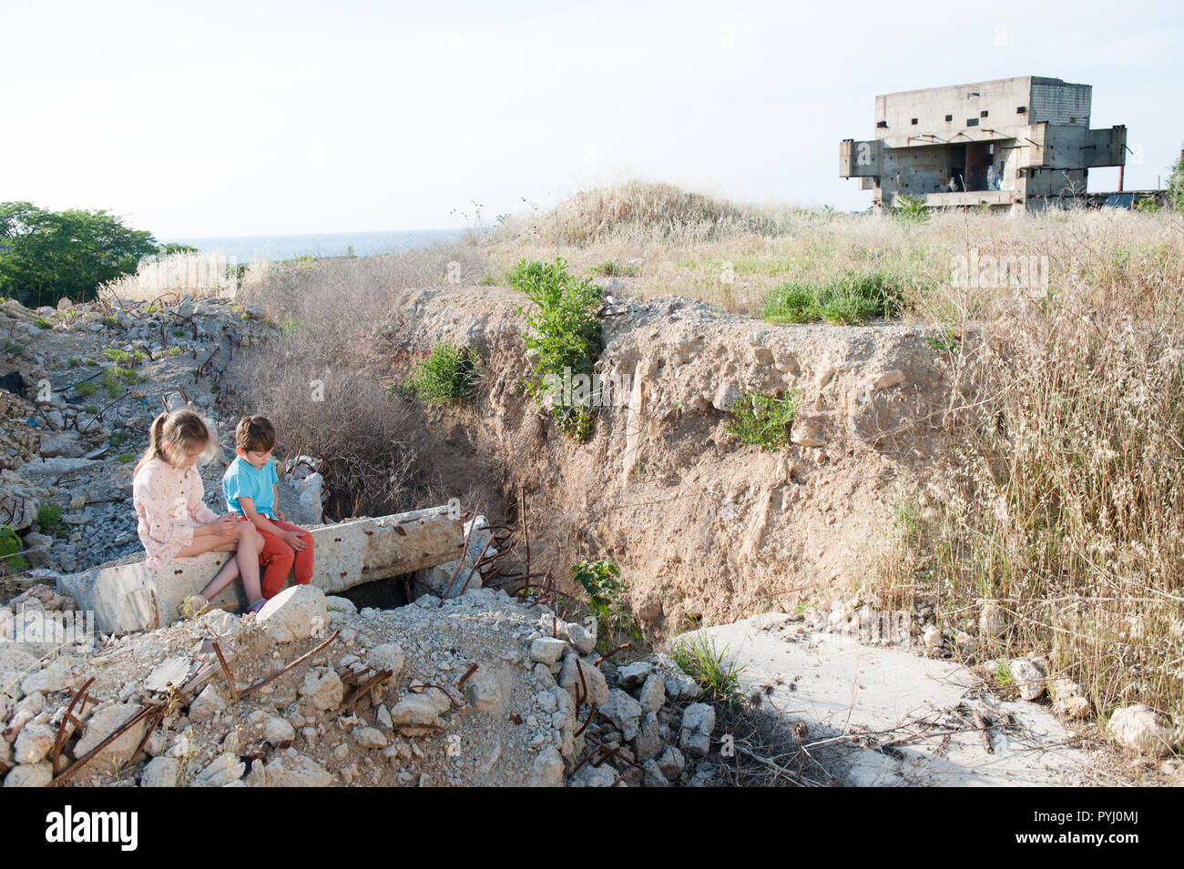 concept of two poor refugee children sitting on ruins of their house in war conflict zone - Stock Image