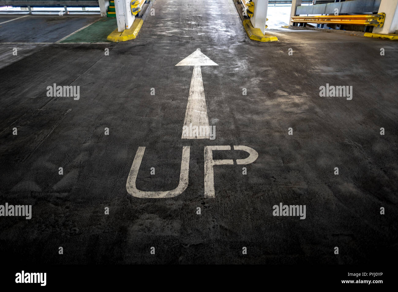 Up and arrow painted on tarmac in a multistory garage - Stock Image