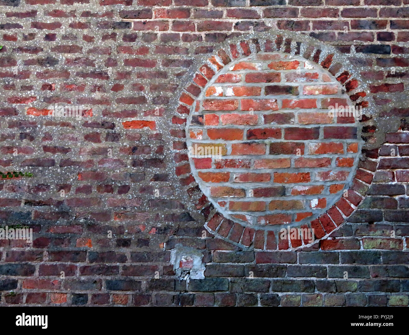 Bricked up round window opening using contrasting red bricks in Bawtry South Yorkshire England - Stock Image